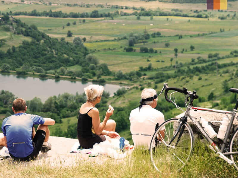 3 cyclists and a bike overlooking the plains on a cycling holiday in Albania