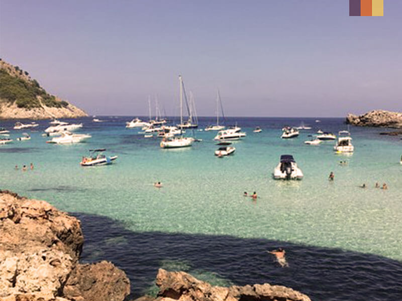 Crystal clear sea with multiple boats and people swimming seen on unexplored coast of Mallorca cycling holiday