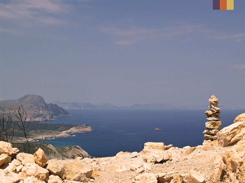 Rocks overlooking the Mediterranean sea with views of the mountains seen on unexplored coast of Mallorca cycling holiday