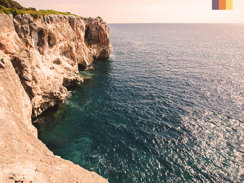 The ocean with jagged rocks and a cliff seen on unexplored coast of Mallorca cycling holiday