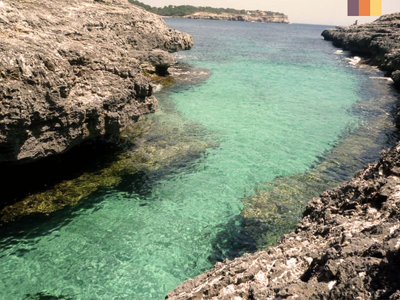 Glistening turquoise ocean with rock formations on each side seen on unexplored coast of Mallorca cycling holiday