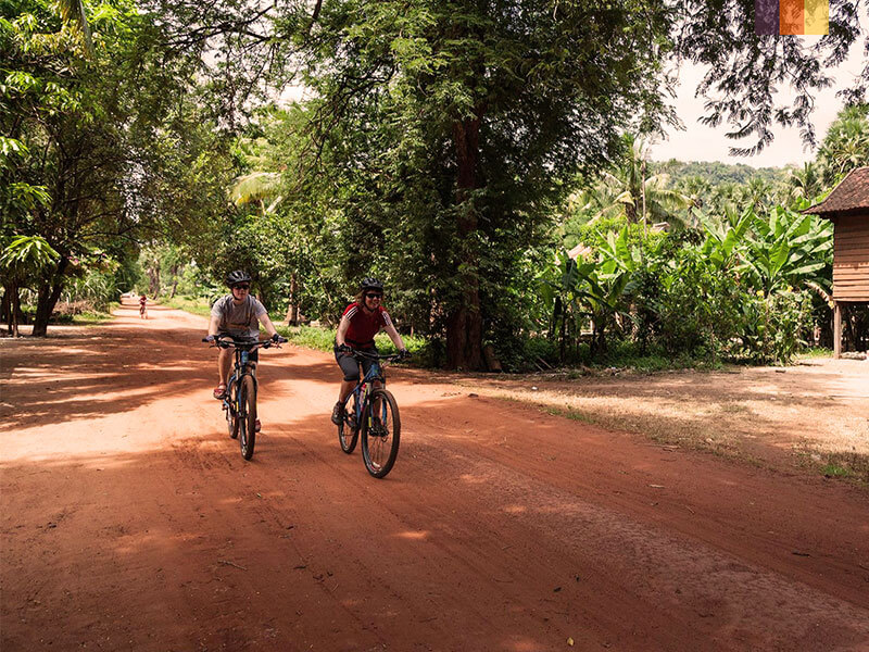Two cyclists on a dirt track riding through a Cambodian village