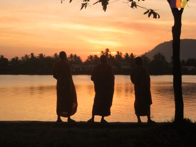Three monks stood by a lake watching the sun set seen on a Cambodia cycling holiday