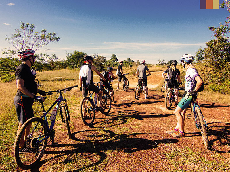 A group of cyclists stopped on a dirt track in the heart of Cambodia