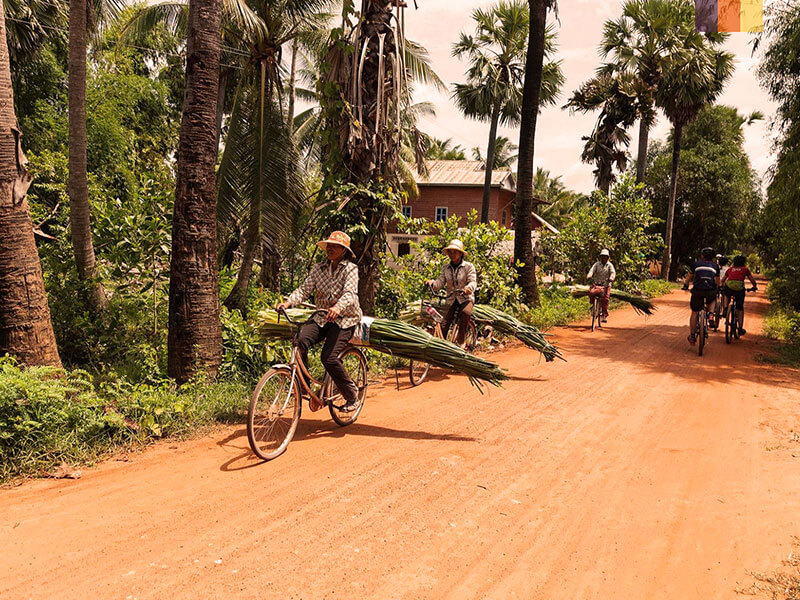 Two local Cambodians riding down a dirt track, seen on a cycling holiday in Cambodia