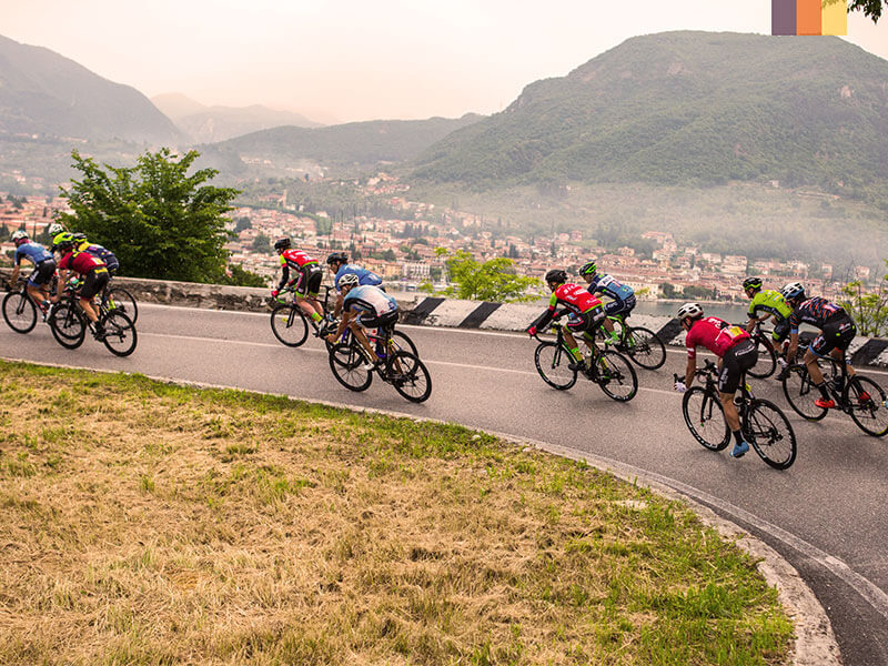 A group of cyclists descending over Lake Garda on a cycling holiday at the Colnago Granfondo