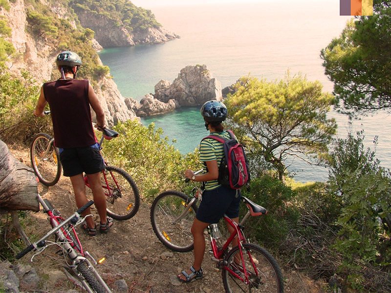 Two cyclists taking in the sea drom a hill above on a cycling holiday in Croatia