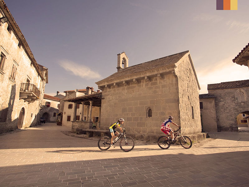 Two people cycling through a medieval town in Croatia