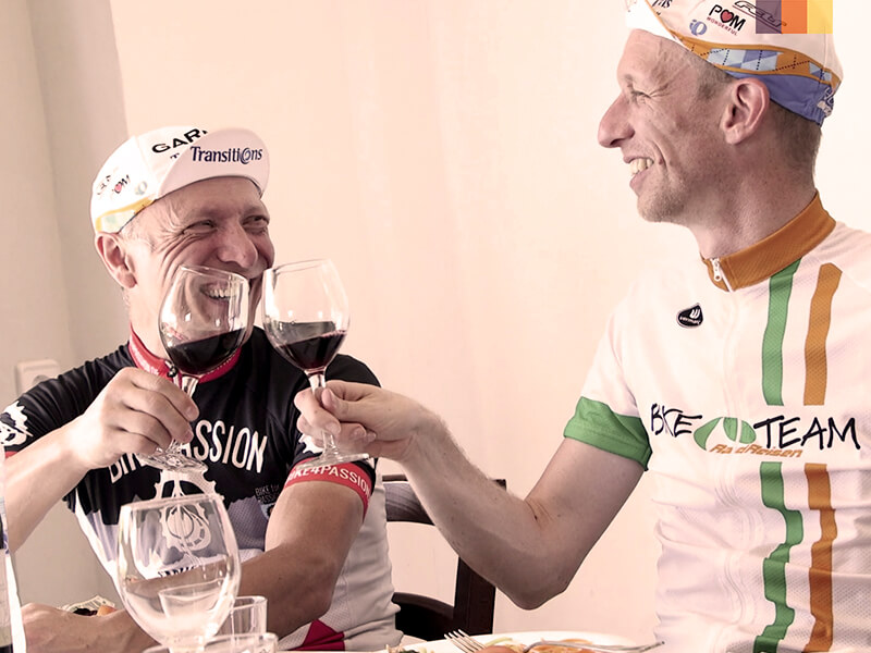 Two men enjoying a glass of wine after cycling
