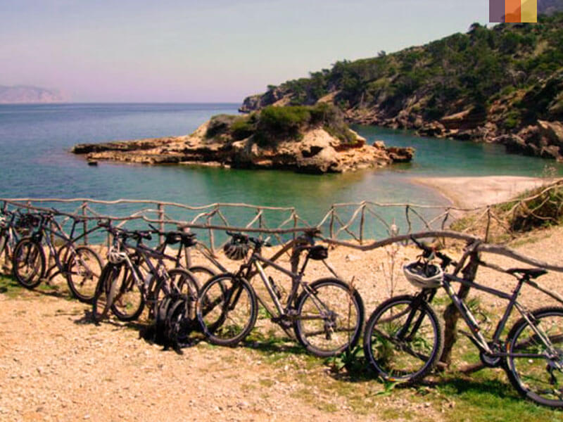 Bikes lined up against a fence by the sea in Mallorca