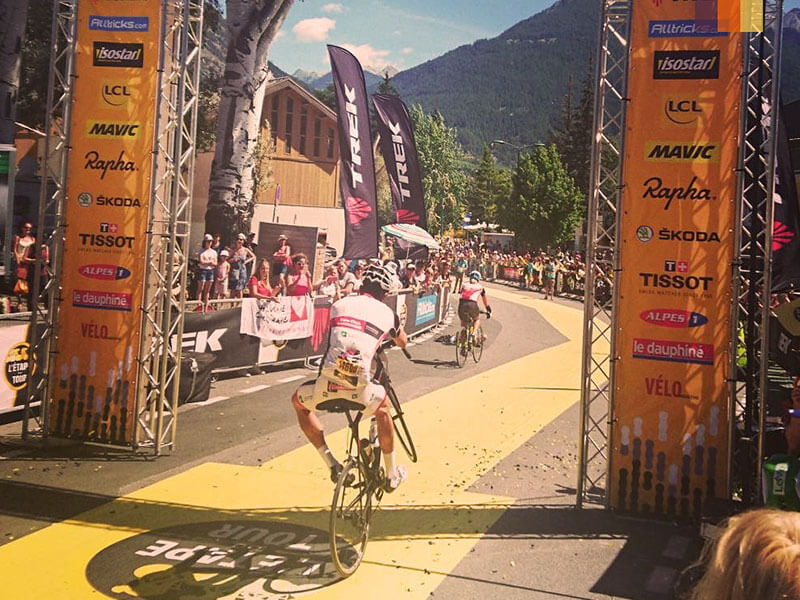 Cyclist doing a wheelie under the arrival sign of the Etape du Tour 2017 in Briancon, France