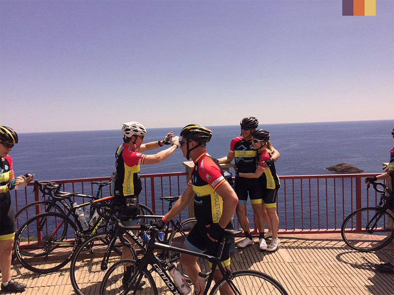 Cyclists stopping to take photos by the sea