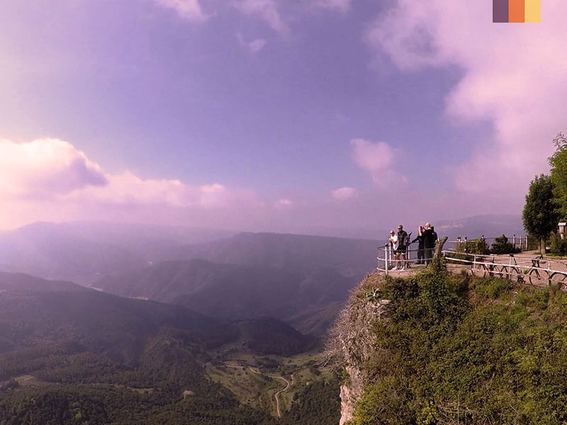 A group of people looking at the mountains from a viewing platform