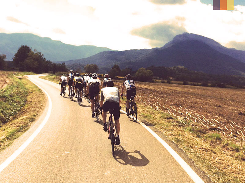 A group of cyclists on a road towards mountains surrounded by soil fields