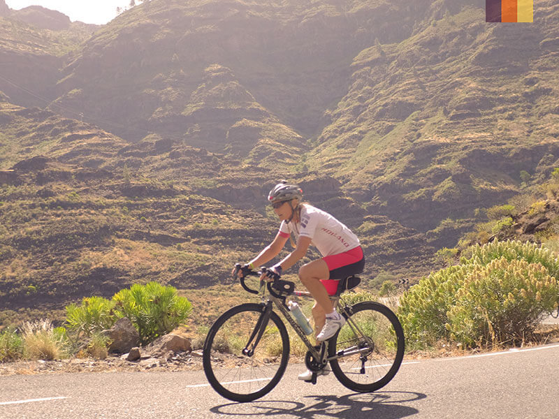 A lone female cyclist on a cycling holiday in Gran Canaria with moss covered mountains