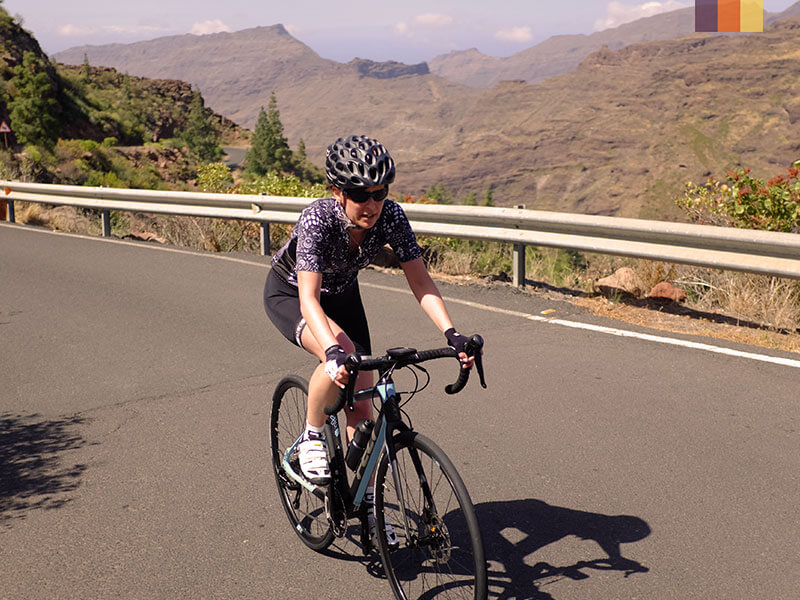 A lone female cyclist climbing a hill in Gran Canaria on a cycling holida
