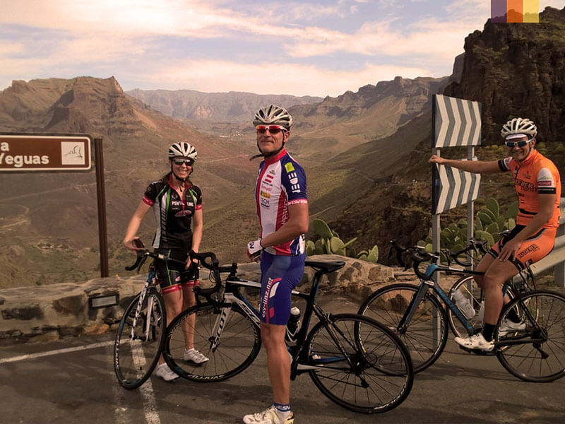 Two male and a female cyclist at the top of a climb in Gran Canaria on a cycling holiday