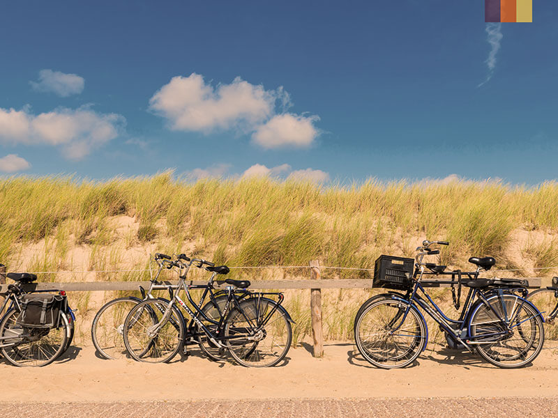 Four bikes leaning against a fence next to a beach on a cycling holiday in Holland