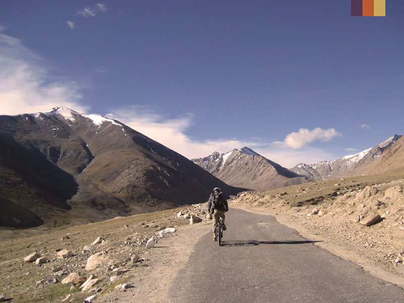 A solo male cyclist riding through the mountains of northern India