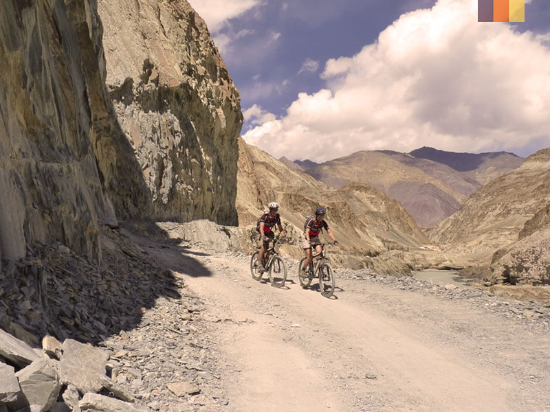Two cyclists riding through the rocky mountains on a cycling holiday in India
