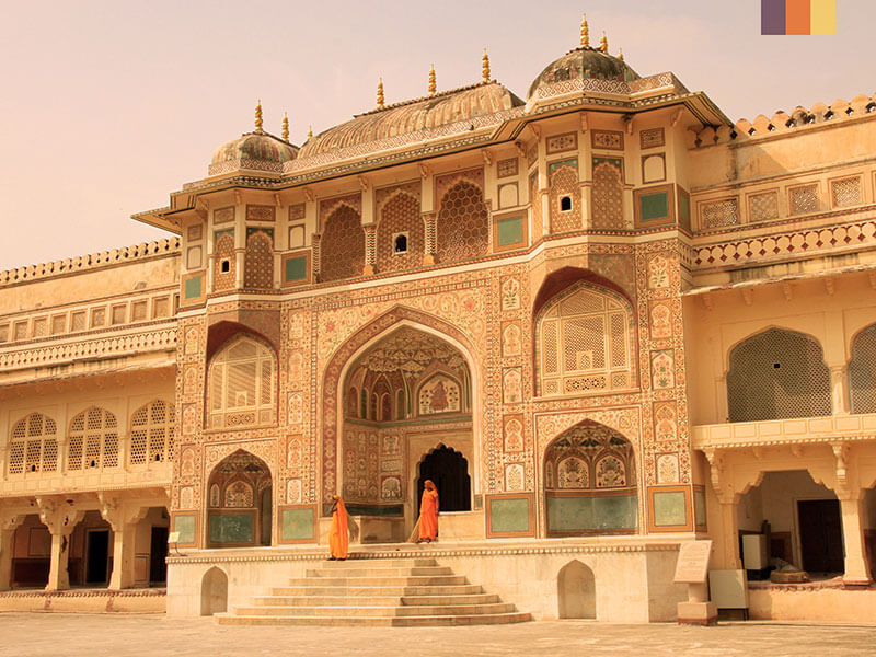 The beautiful Amer Fort in Rajasthan with two monks coming out the entrance