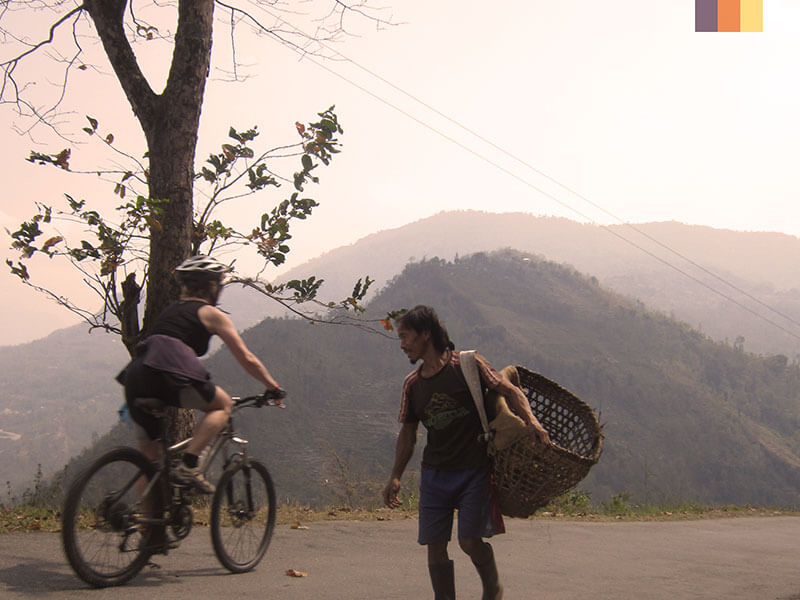 A female cyclist and local man carrying a basket seen on India cycling holiday