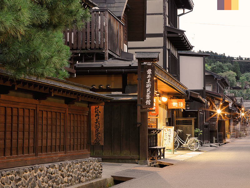 Street view of a Japanese town with a bicycle propped up against a wall