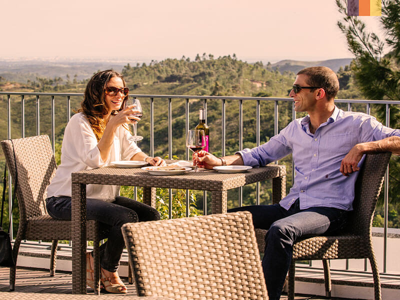 A couple relaxing enoying a meal and wine on a balcony in Portugal