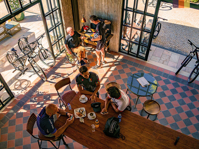 A group of cyclists enjoying food and relaxing at the cafe in The Campus resort Quinta da Lago