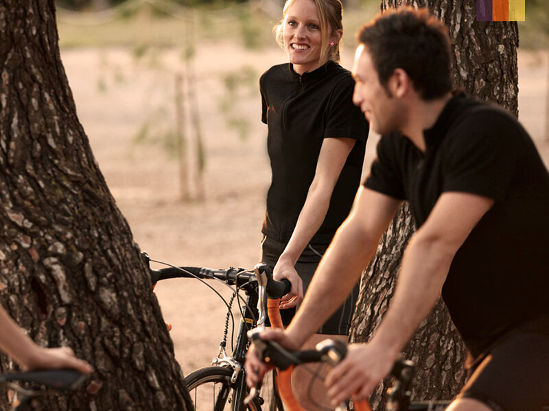 two cyclists amongst the trees on the beach of Formentor in Mallorca