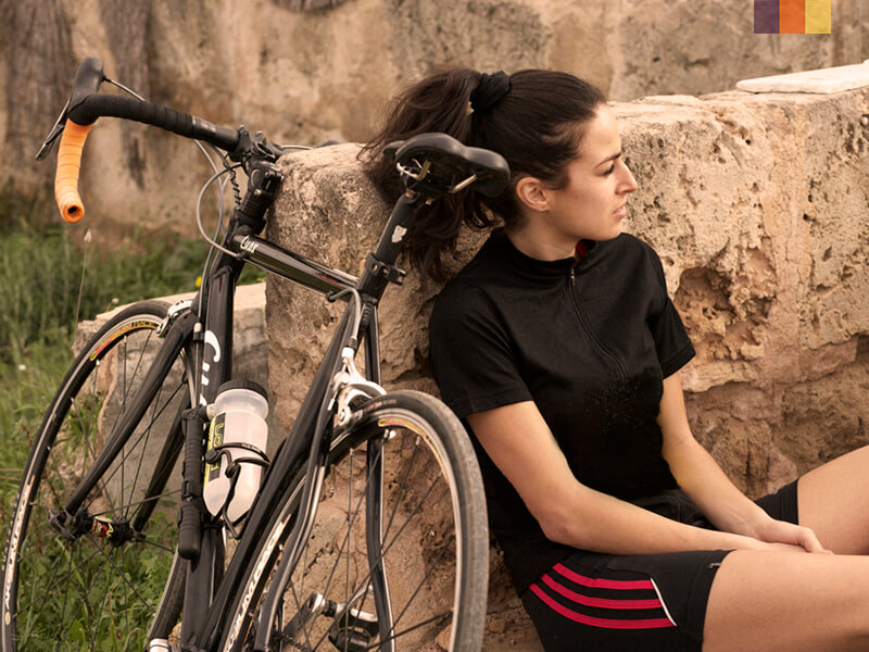 A cyclist leaning up against a stone wall in Mallorca, with her bike alongside her