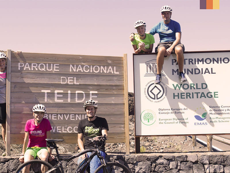 A group of cyclists by the Teide National Park sign