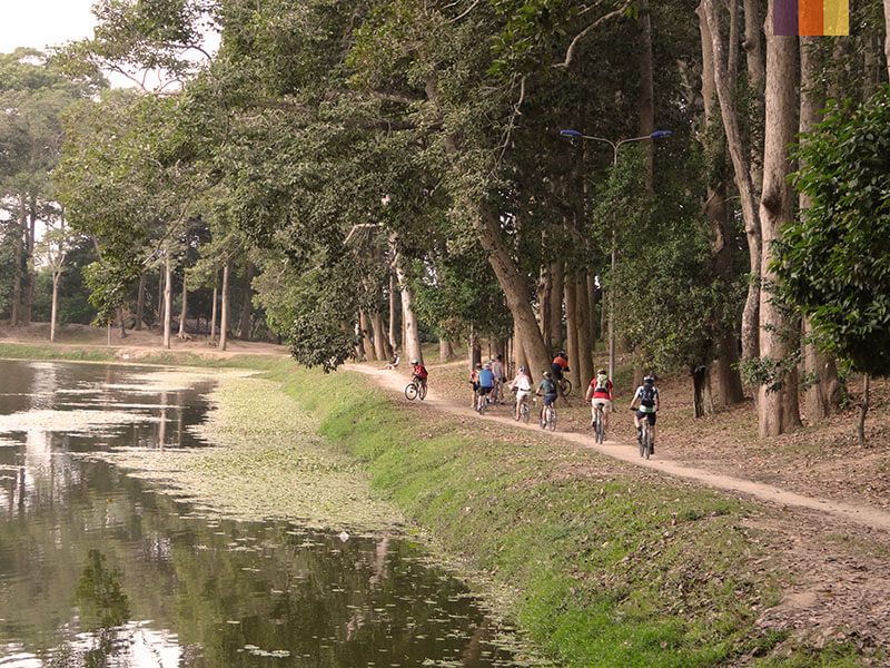 A group of cyclists riding down a path next to a river in central Thailand