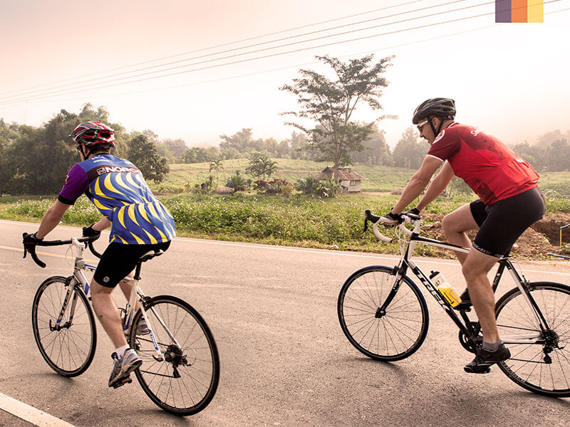 Two cyclists road biking on a northern Thailand on a cycling holiday