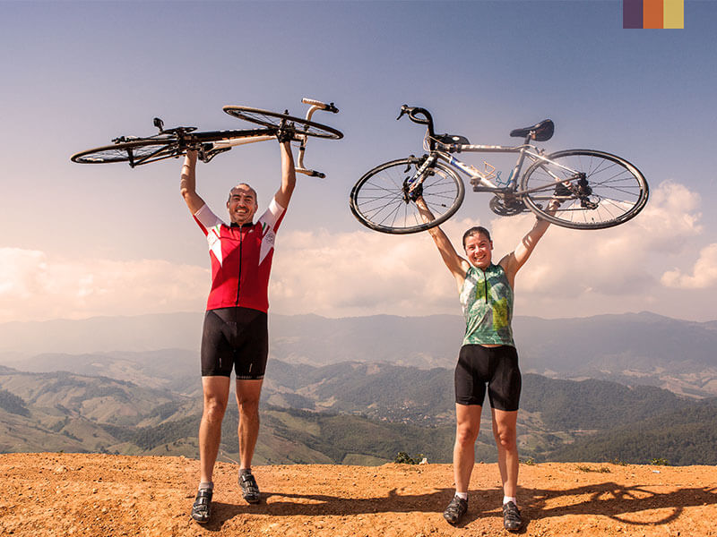 Two cyclist hold their bikes in the air against a backdrop of mountains on a North Thailand cycling holiday
