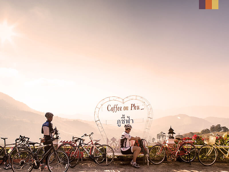 Two cyclists take a break by a Coffee on Phu sign