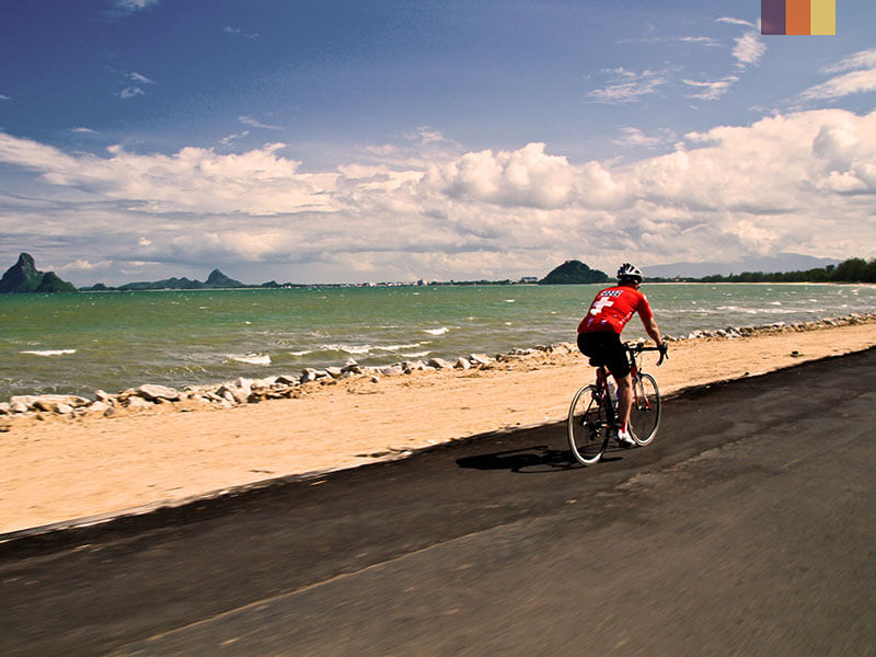 A road cyclist riding down the beach in Phuket, Thailand