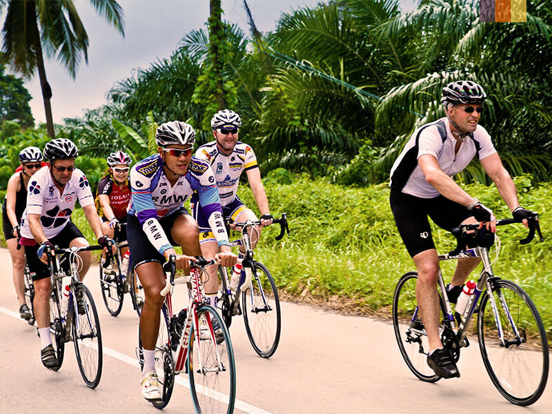 a group of cyclists road biking along the southern coast of Thailand