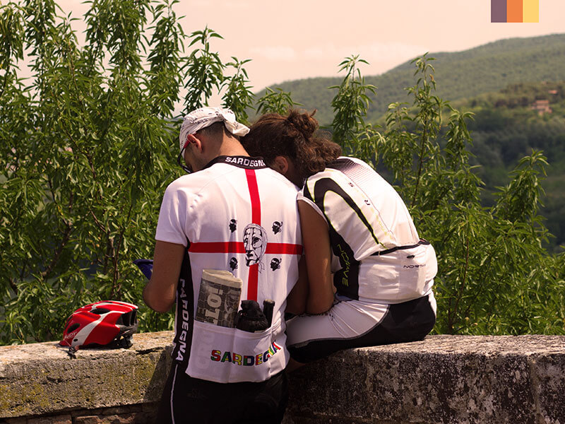 Two cyclists reading a map in the Tuscan hills on a cycling holiday