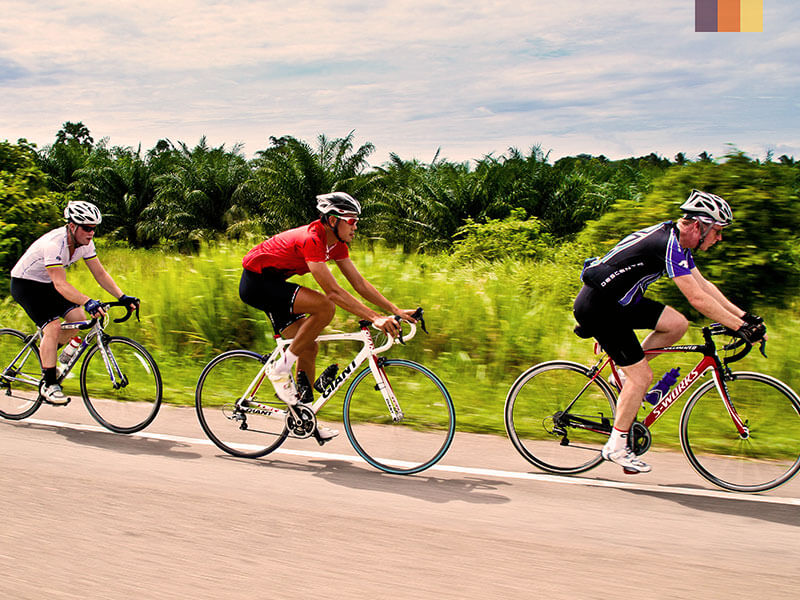 Three cyclists on a road beside fields in Asia