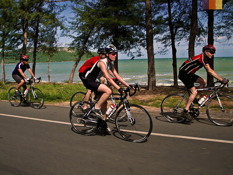 Four road cyclists riding alongside the beach in vietnam  on a cycling holiday