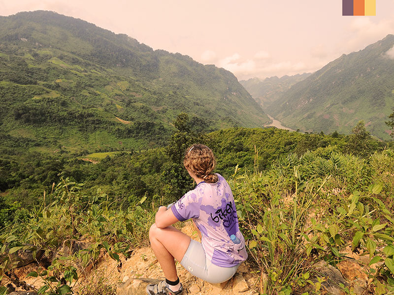 A woman in Vietnam taking a break and looking at the view of mountains, greenery and a river on her cycling holiday