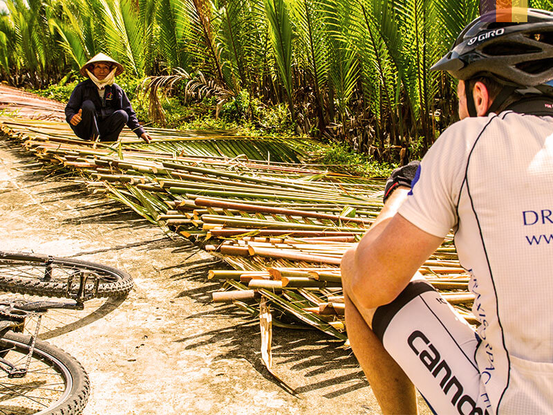 A man on a cycling holiday in Vietnam taking a photo of a local woman