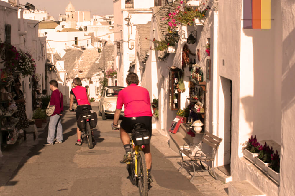 A cyclist riding through the whitewashed streets of Ostuni in Puglia Italy