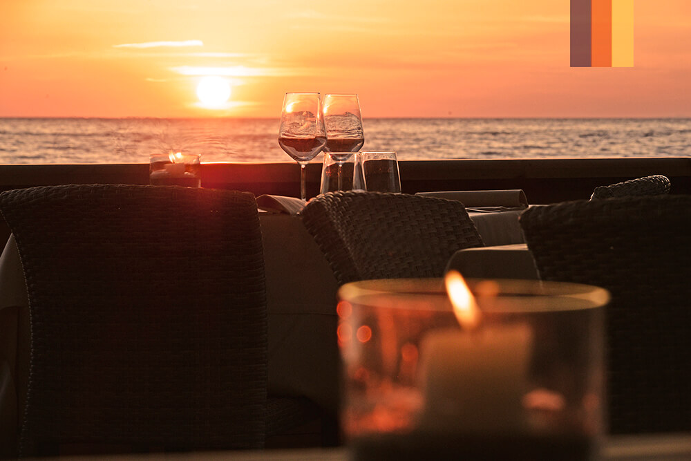 Two glasses of wine on a table on the beach at sunset at the Paradu Eco Resort