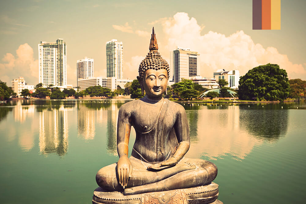 A giant Buddha in the foreground of a photo in Sri Lanka