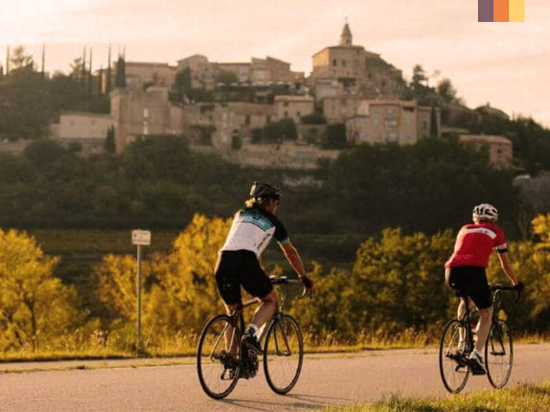 Two cyclist on a cycling holiday in Provence passing a town