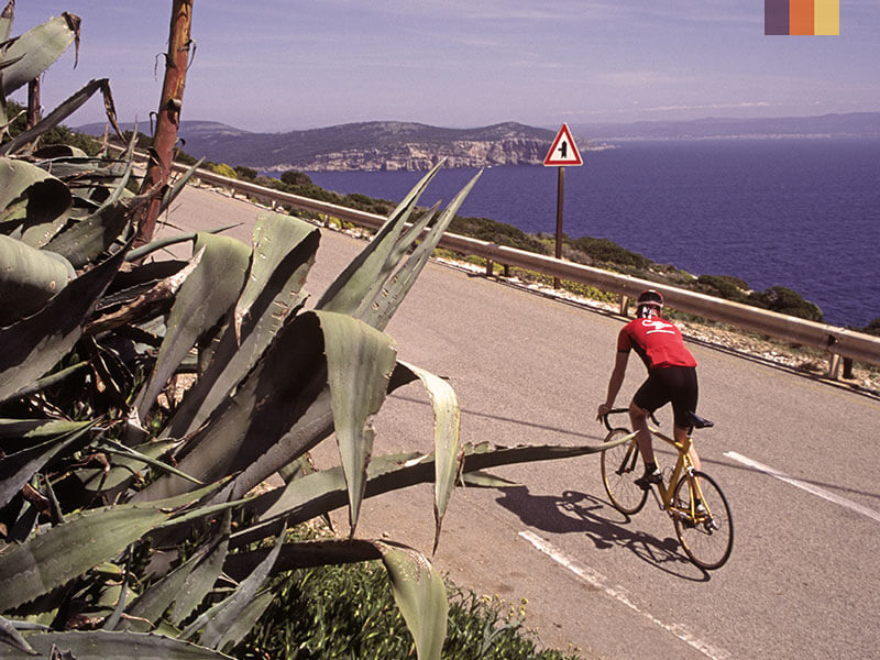 A lone cyclist on a road above the sea
