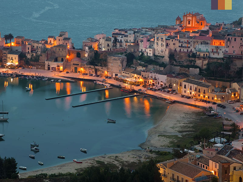 Sicily peninsula at dusk dimly lit with coloured buildings and the sea behind