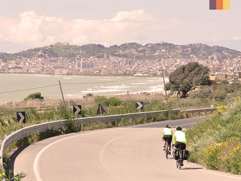 Two cyclists on a road cycling round a corner with a city on the other side of the bay